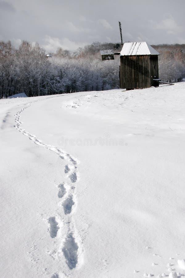 Человеческие трассировки в снеге водя к старой мельнице стоковое фото