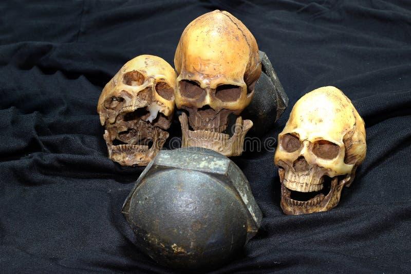 Человеческие черепа и тяжелые черные гантели на черной предпосылке стиль и разминка натюрморта концепции стоковое фото rf