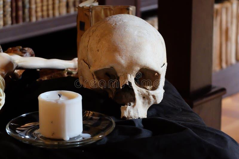 Человеческие череп, крест и свеча на таблице с черной тканью в исторической библиотеке стоковое фото rf