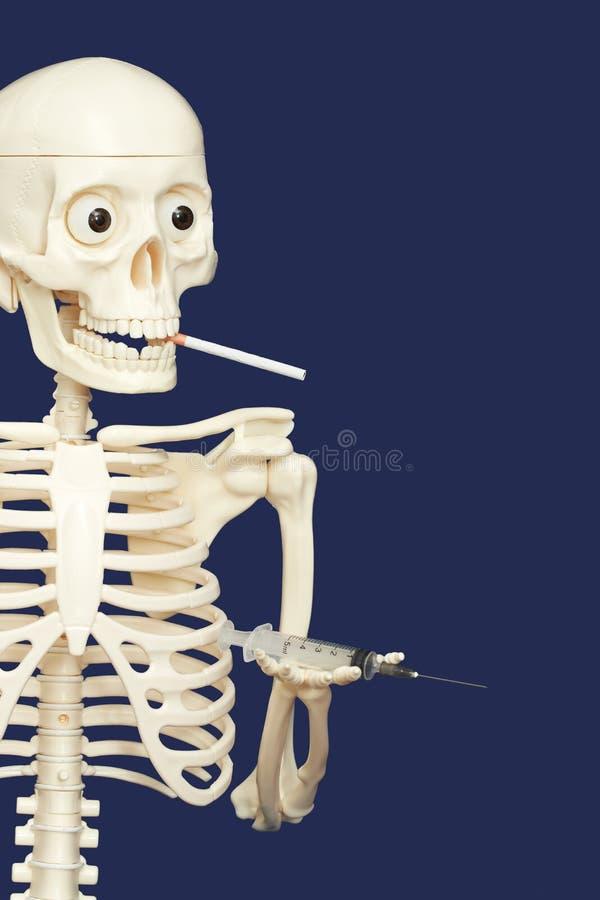 Человеческий скелет куря и используя лекарства - смерть стоковые фото