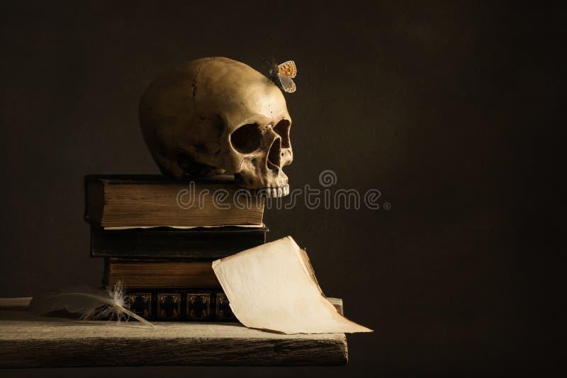 Человеческий череп с бабочкой и пустой страницей с пером стоковые фотографии rf