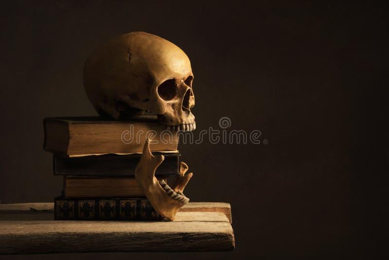 Человеческий череп с Jawbone на старых книгах стоковое фото