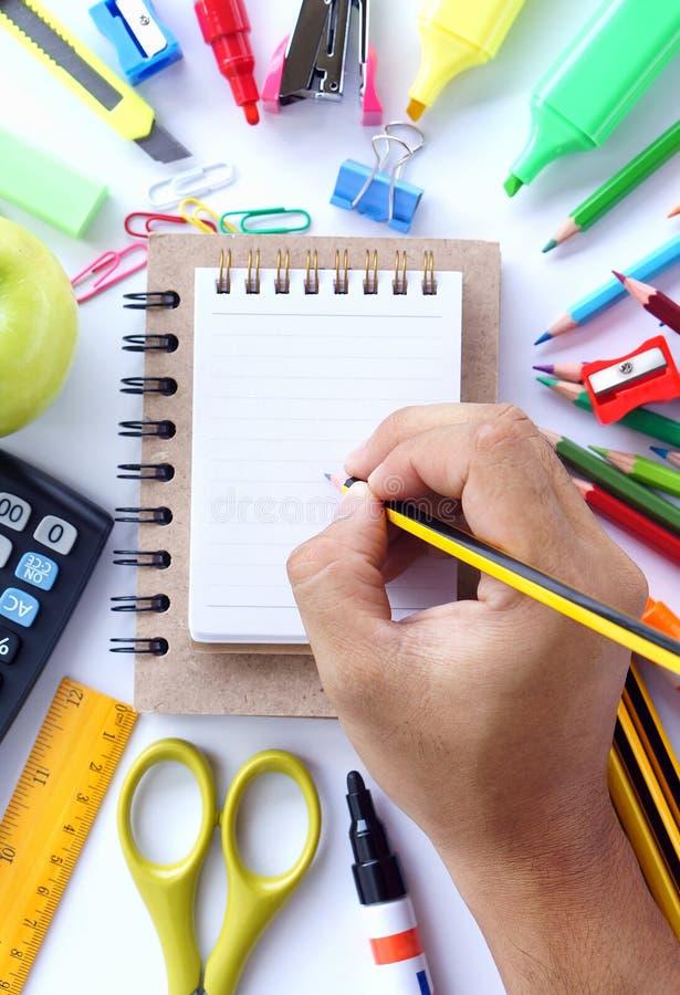 Человеческое сочинительство руки на пустой малой тетради с канцелярскими принадлежностями школы стоковое фото rf