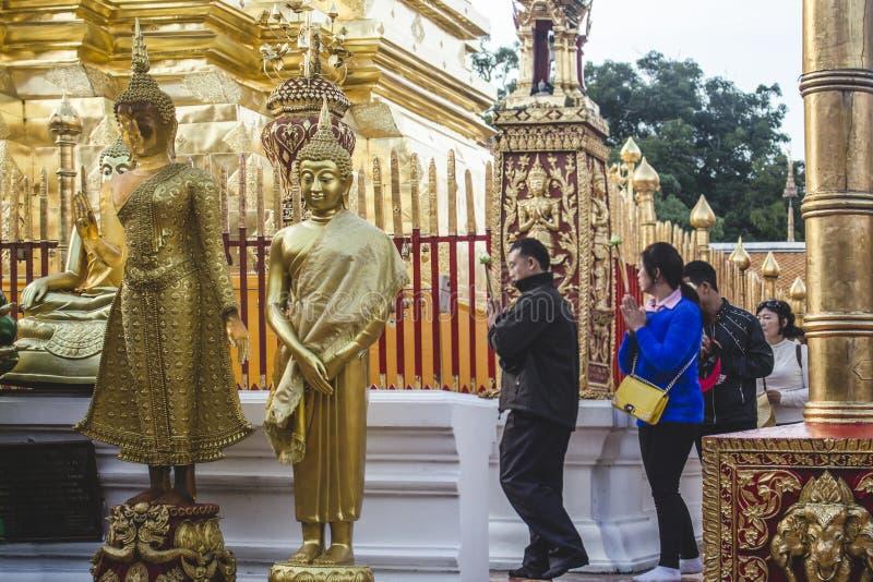 Чиангмай, Таиланд - ноябрь 2017: Статуи Будды рядом с молить азиатские людей оплачивая их уважения на Doi Suthep стоковое фото