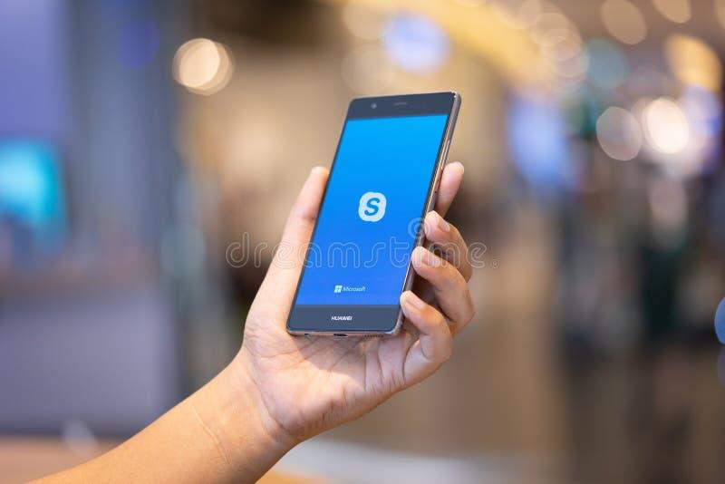 ЧИАНГМАЙ, ТАИЛАНД - октябрь 28,2018: Человек держа HUAWEI с приложениями skype r стоковое изображение rf