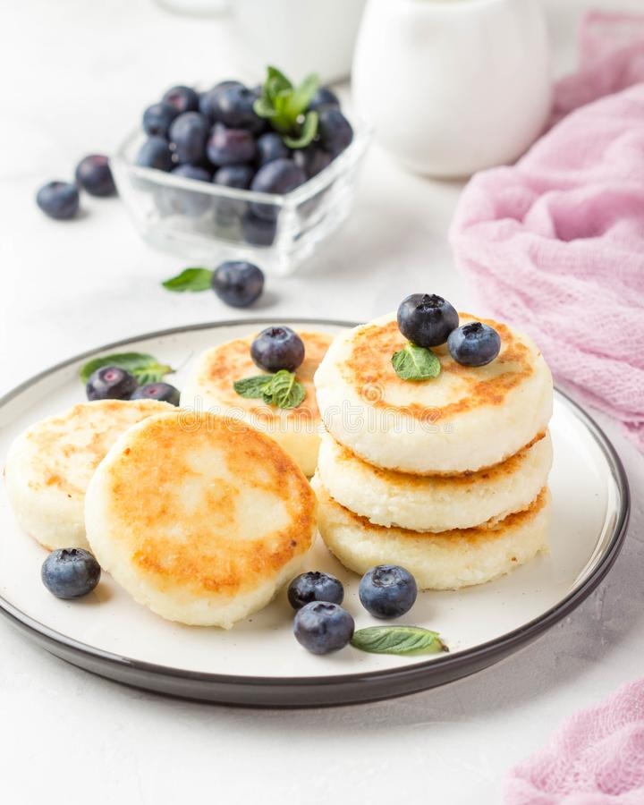 Чизкейки от творога, очень вкусного завтрака, традиционных русских сладких блинчиков С голубикой, мятой и соусом стоковая фотография rf