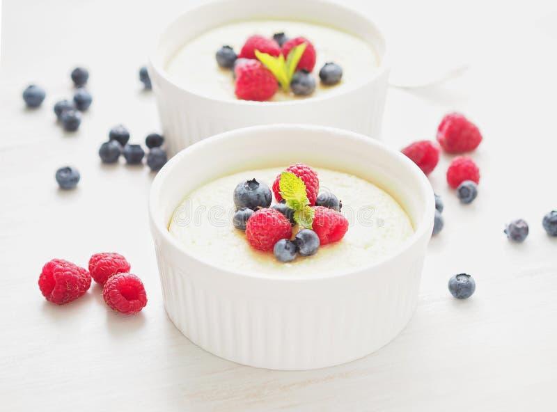 чизкейк украшенный с полениками, голубиками и мятой в 2 ramekin, очень вкусный десерт для завтрака, взгляда со стороны стоковые изображения