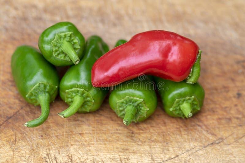Чилей Jalapeno Capsicum перцы annuum горячие, группа в составе зеленая и красный цвет приносить на деревянной разделочной доске стоковая фотография