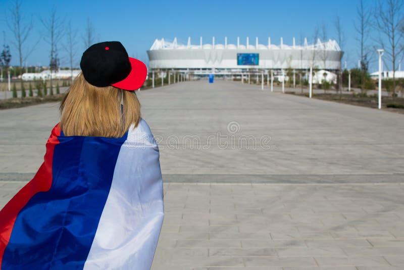 Чирлидер девушки возглавляя к футбольному стадиону с флагом России стоковое изображение