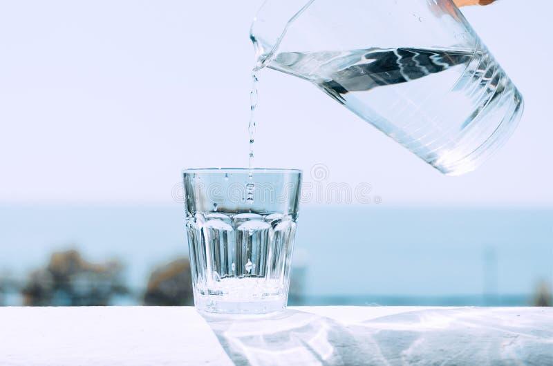 Чистая вода от кувшина полита в стеклянный beaker Стекло с водой на предпосылке моря стоковое фото rf