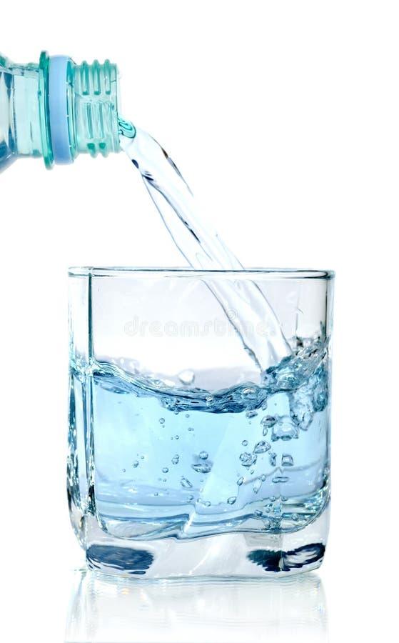 Чистая вода будучи политым в стеклянную изолированную чашку стоковая фотография