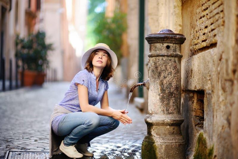 Чистая вода молодой женщины выпивая от фонтана в Риме, Италии стоковое фото rf