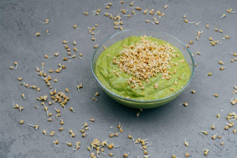 Чистая концепция еды и вытрезвителя Зеленый smoothie vegan в шаре Пусканные ростии семена вокруг Здоровое зеленое органическое сы стоковая фотография rf