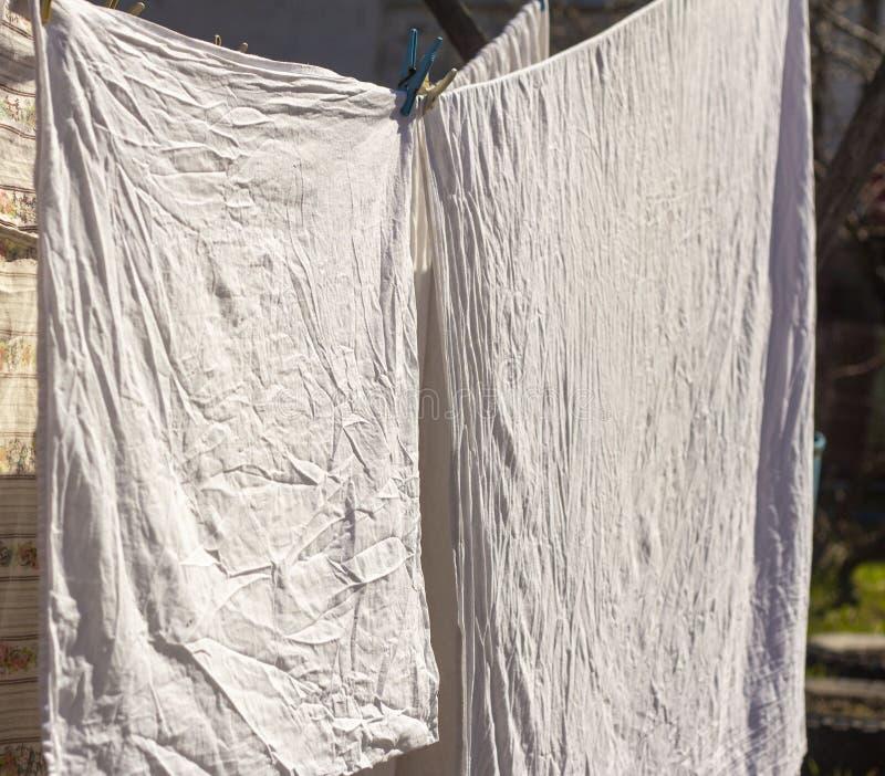 Чистая мытая постельное белье высушивается на свежем воздухе в деревне стоковые изображения
