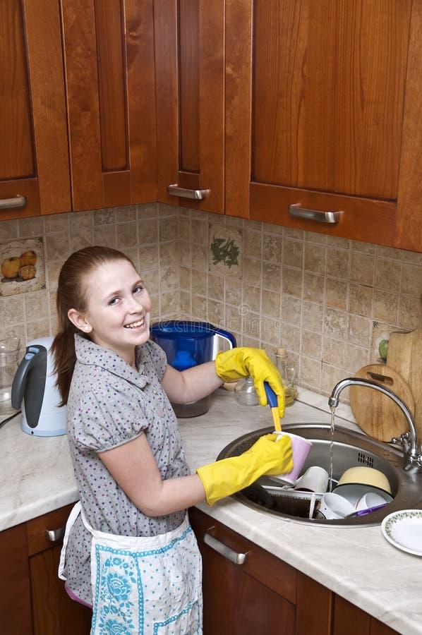 чистка dishes детеныши девушки стоковая фотография