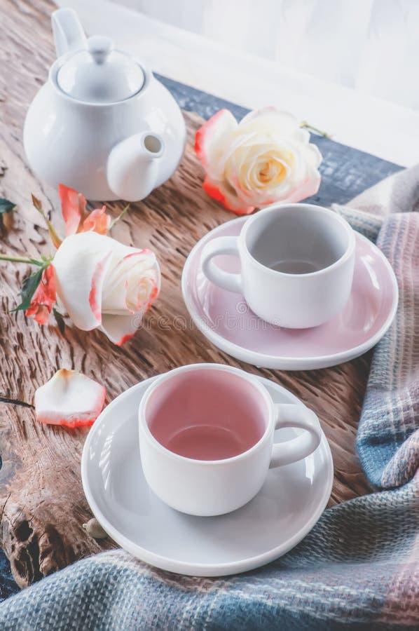 Чисто комплект кофе или чая Пара элегантных чашек света фарфора - серых и пастельных розовых на уютной предпосылке стоковые фото