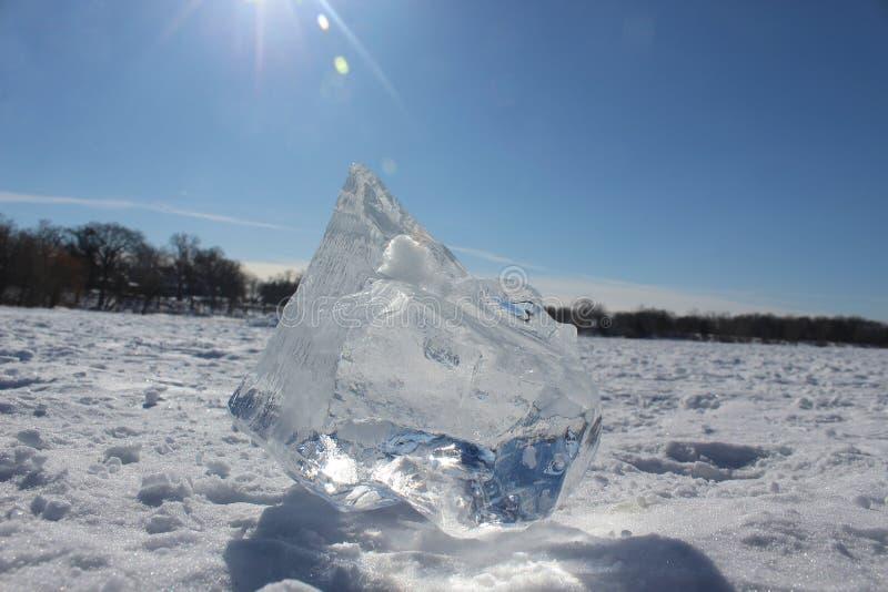 Чисто ледяной кусок, сидящий на снегу на замороженном озере стоковые фотографии rf