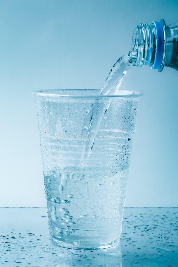 Чисто свежая вода льет в стеклянную или пластичную чашку в падениях близко вверх, здоровое питье стоковые фото