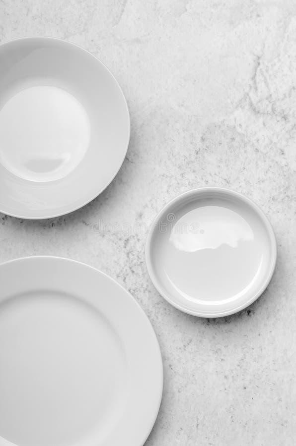 Чистые маленькие белые плиты на светлой каменной предпосылке Кухня Minimalistic, блюда Взгляд сверху, плоское положение стоковое фото