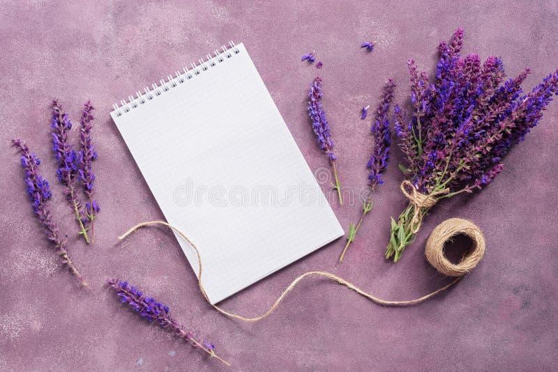 Чистый блокнот и букет цветков salvia на красивой абстрактной пурпурной предпосылке Модный творческий план : стоковые изображения