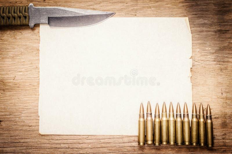 Чистый лист бумаги, нож и пули стоковые изображения