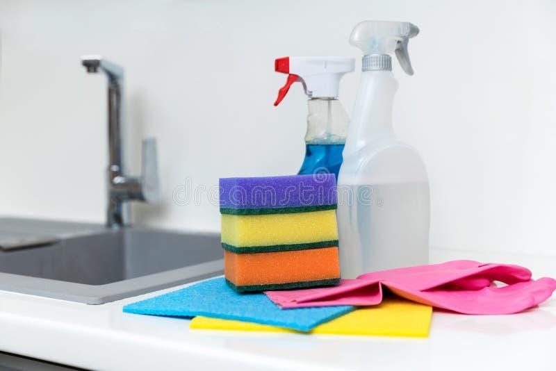 Чистящие средства и оборудование кухни на белом worktop стоковые фото