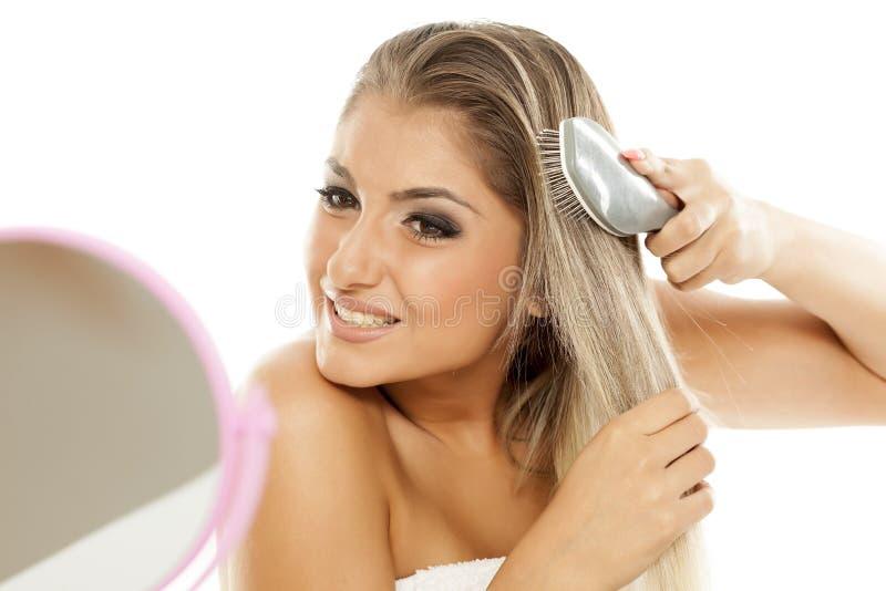чистя щеткой волосы ее женщина стоковая фотография rf