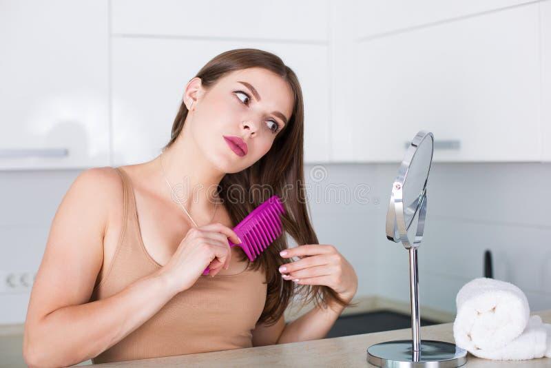 чистя щеткой волосы ее женщина стоковое изображение rf