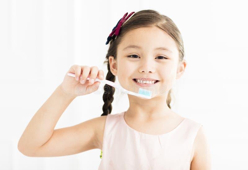 чистя щеткой девушка ее маленькие зубы стоковая фотография rf