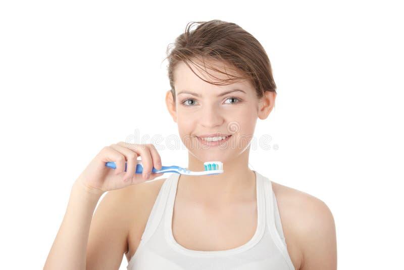 чистя щеткой девушка счастливо ее зубы молодые стоковое изображение