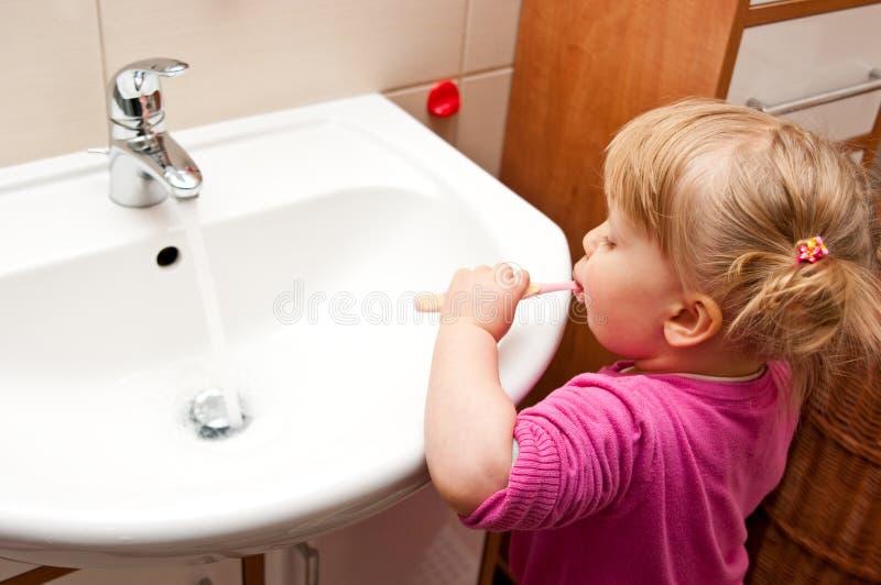 чистя щеткой зубы девушки стоковые изображения rf