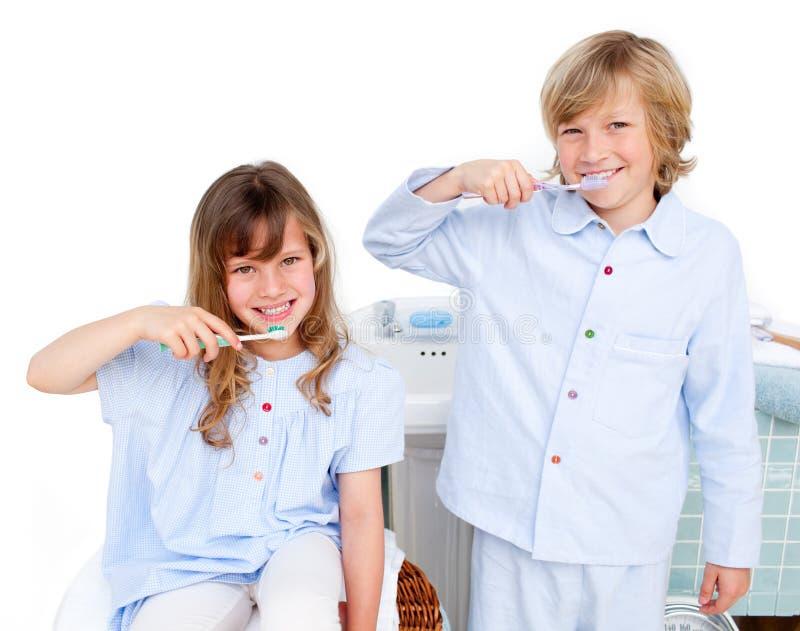 чистя щеткой зубы детей милые их стоковые фото
