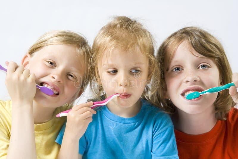 чистя щеткой зубы детей стоковые фото