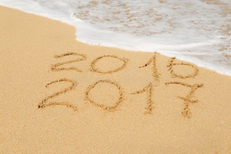 Числа 2016 и 2017 на песке стоковое изображение