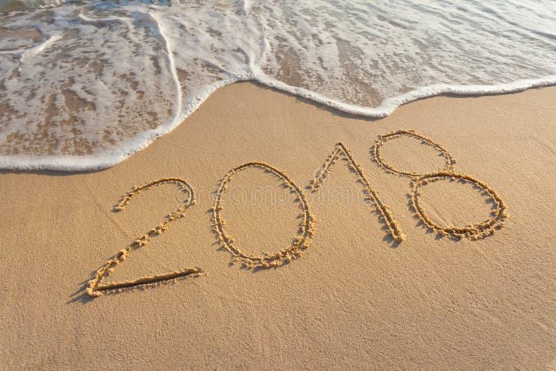 Число 2018 на красивом пляже на заходе солнца стоковое изображение