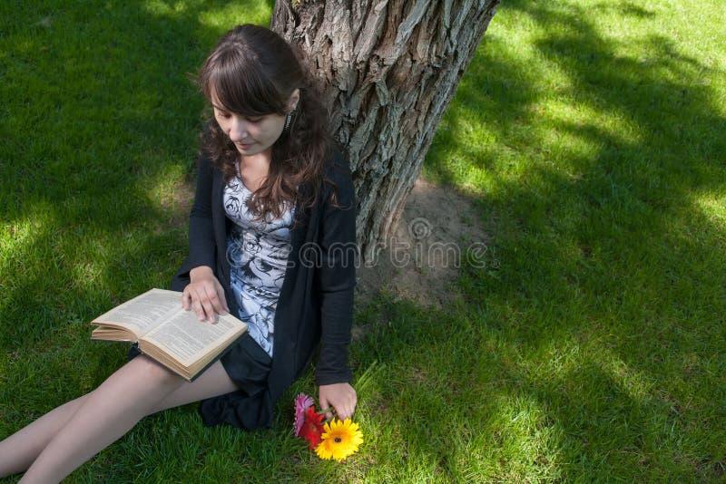 Читать внутри парк Милая прочитанная девушка сидя на траве и старой книге стоковое фото