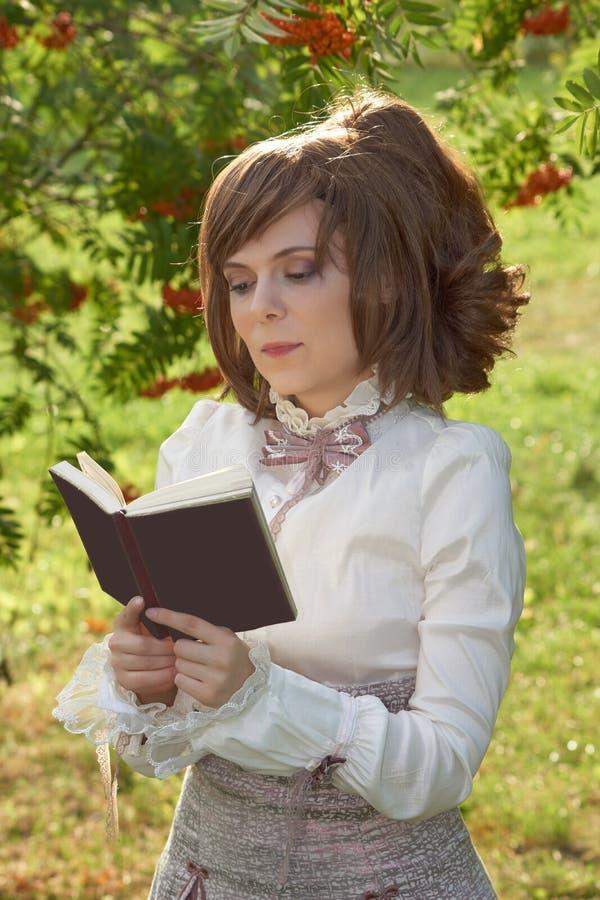 Читать книгу в парке стоковое изображение