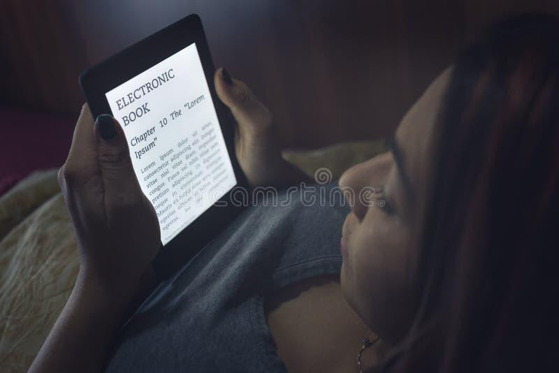 Читать ebook в кровати стоковое изображение rf