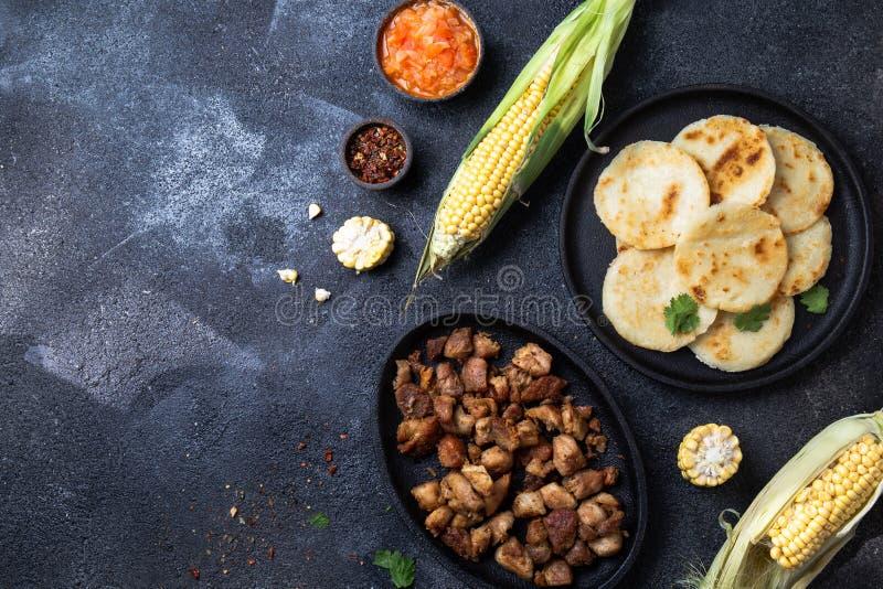 чолумбийская еда Маис AREPAS и зажаренный томатный соус ans chicharron свинины колумбийский Взгляд сверху Черная предпосылка стоковые изображения