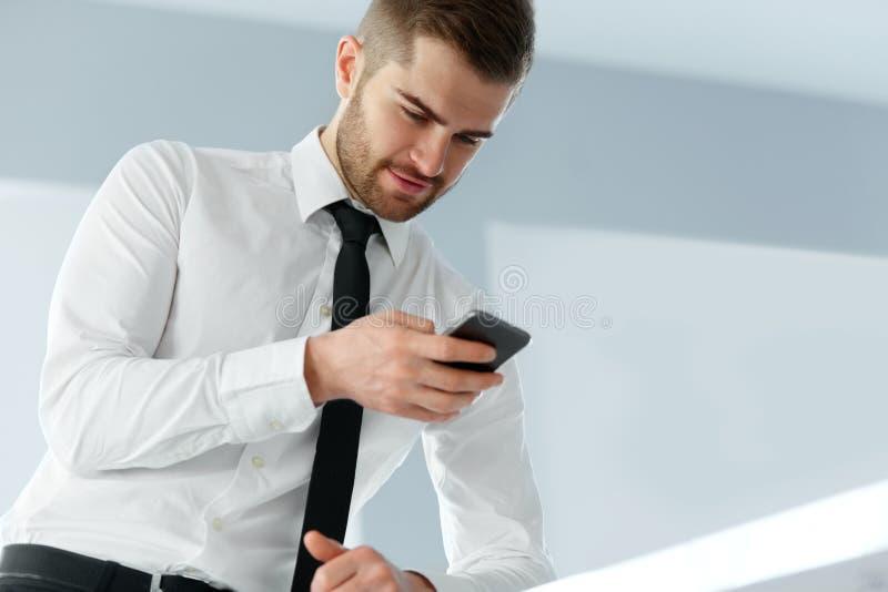 Чтение бизнесмена что-то на экране его сотового телефона стоковые фотографии rf