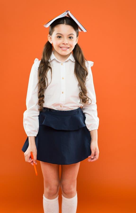 Чтение всегда отличная идея Маленькая книга удерживания школьницы с идеей на голове Небольшой милый ребенок имея идею гения дальш стоковые фотографии rf