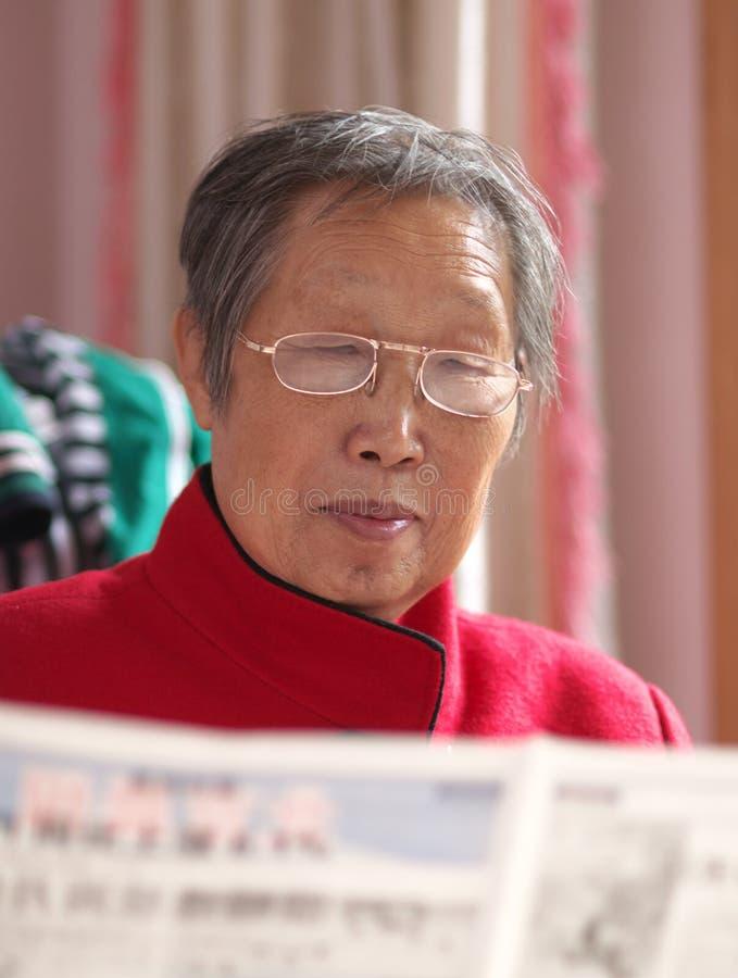 чтение газеты бабушки стоковое изображение