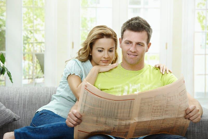 чтение газеты пар стоковые изображения
