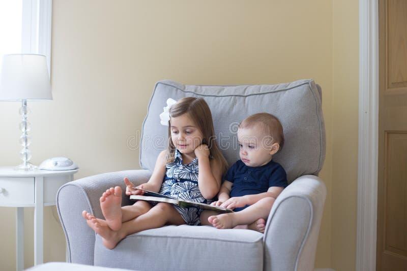 чтение девушки мальчика книги стоковые фотографии rf