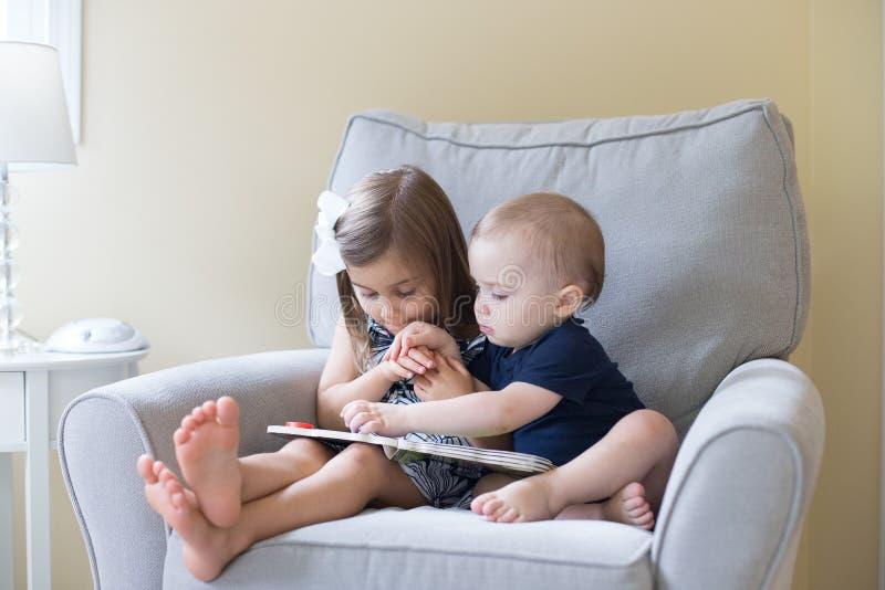 чтение девушки мальчика книги стоковые изображения rf