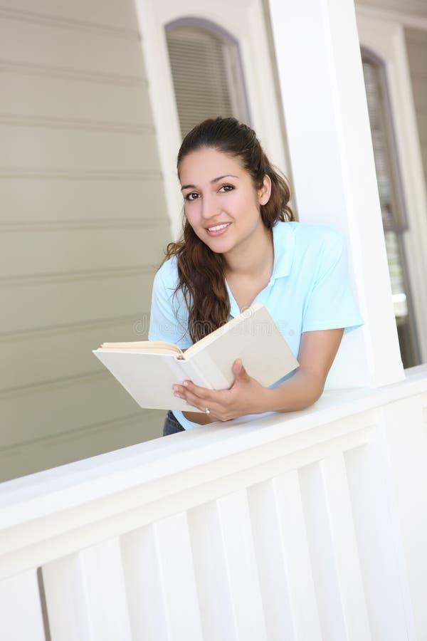 чтение домашнему крылечку девушки милое стоковое изображение