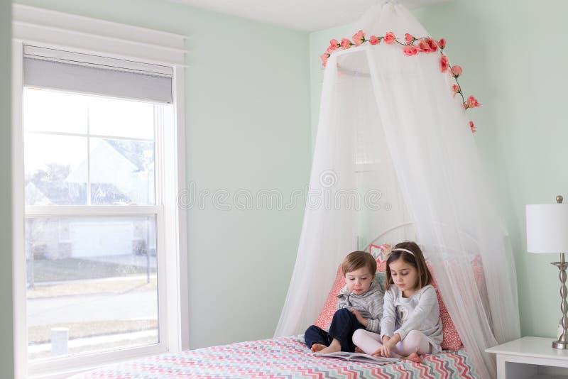 Чтение мальчика и девушки в кровати стоковые изображения