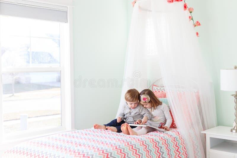 Чтение мальчика и девушки в кровати стоковое фото