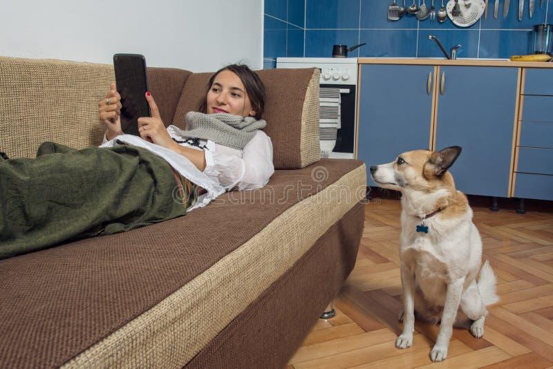 Чтение молодой женщины от ее таблетки и ее собаки стоковые изображения