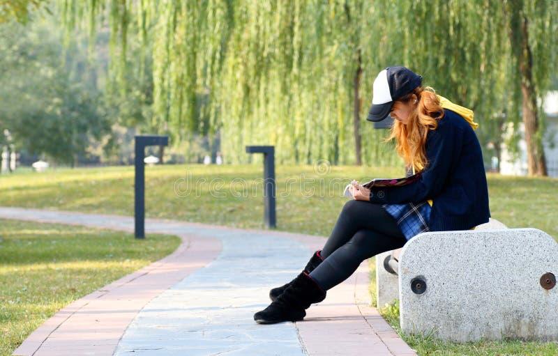 чтение парка девушки стоковые фотографии rf